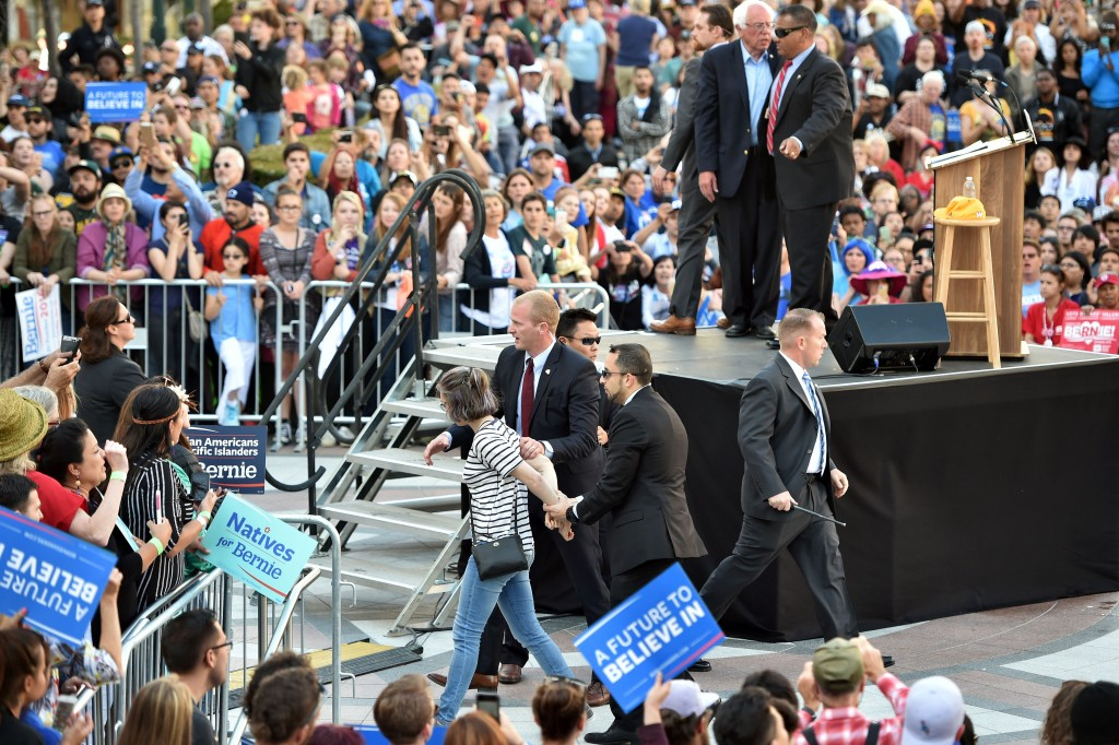 Secret Service agents shield Vermont Sen. Bernie Sanders as others lead a woman away after she and others rushed the stage at a Sanders rally on Monday in Oakland, California. (Josh Edelson/AFP/Getty Images)