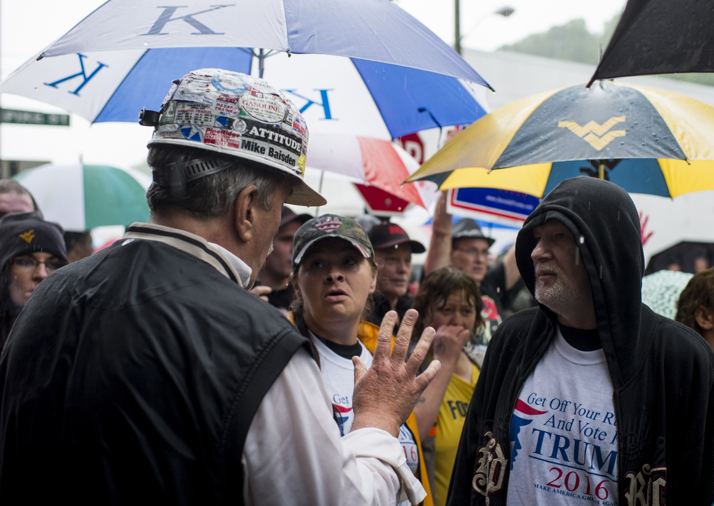 Protesters gather in the rain as presidential candidate Hillary Clinton tours a health and wellness center in Williamson, W. Va. ( Bill Clark/CQ Roll Call)
