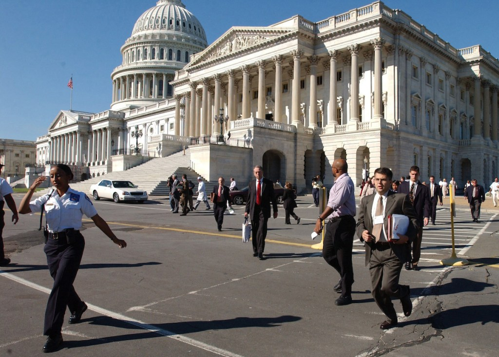 People run from the East Front of the U.S. Capitol during the evacuation after terrorist attacks on the World Trade Center in New York and the Pentagon in Virginia on Sept. 11, 2001. (CQ Roll Call archive photo)