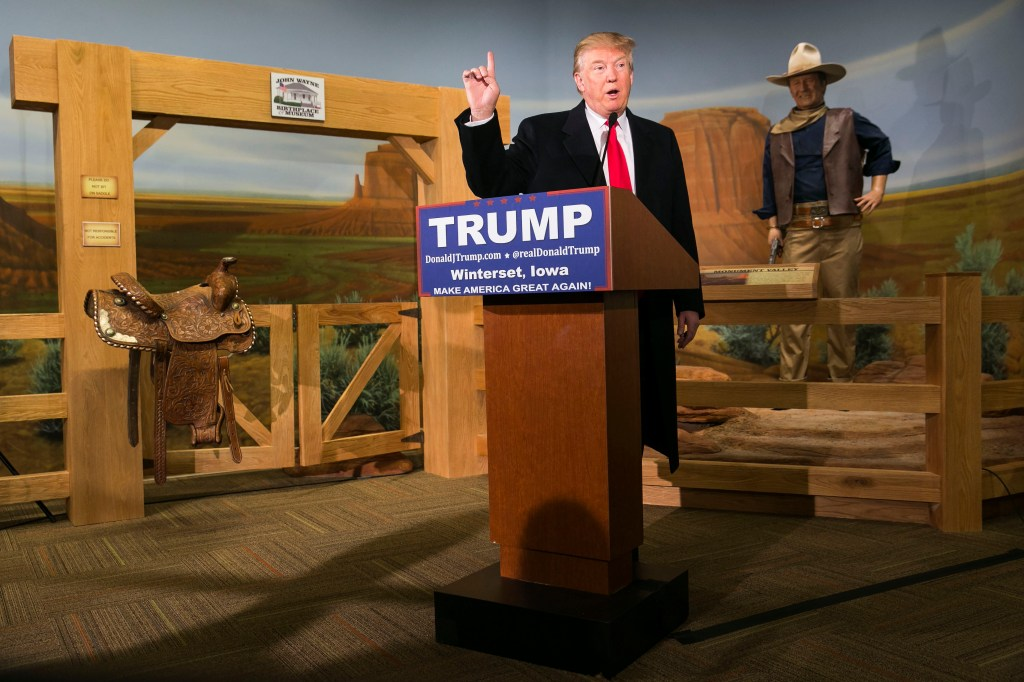 Jan. 19, 2016: A wax statue of John Wayne overlooks Republican presidential candidate Donald Trump as he speaks during a news conference at the John Wayne Museum in Winterset, Iowa. (Al Drago/CQ Roll Call file photo)