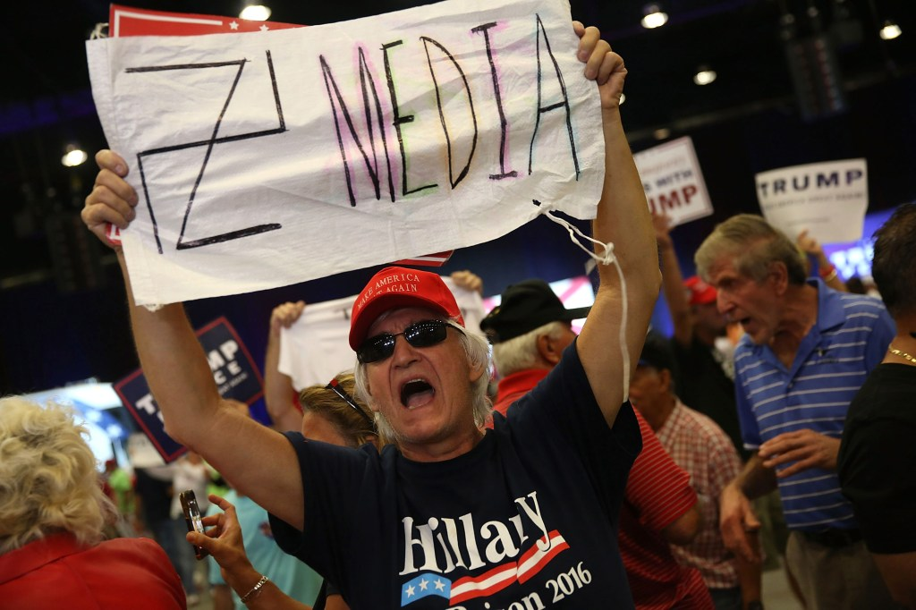 WEST PALM BEACH, FL - OCTOBER 13: A man holds a sign towards the media as he attends a campaign rally for Republican presidential candidate Donald Trump at the South Florida Fair Expo Center on October 13, 2016 in West Palm Beach, Florida. Trump continues to campaign against Democratic presidential candidate Hillary Clinton with less than one month to Election Day. (Photo by Joe Raedle/Getty Images)