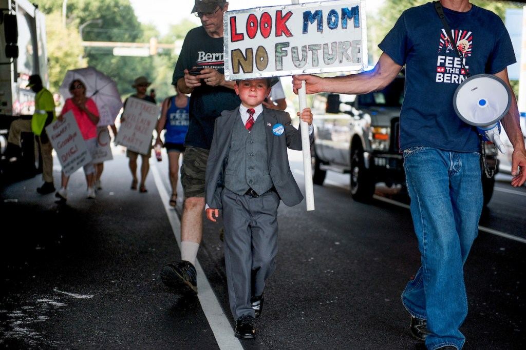 16. July 25: Connor Garrett, 9, of Connecticut, and his father, Dan, walk down Broad Street during a march by supporters of Vermont Sen. <a class=