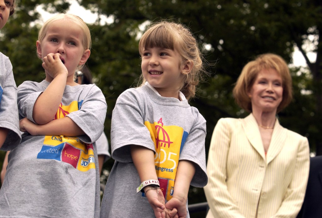 Delegates for the Juvenile Diabetes Research Foundation International (JDRF) Children's Congress 2005, Kendra Parker, 4, of Utah, left, and Madie Poulin, 5, of R.I., wait to perform a song on the West Front of the Captiol, to kick off awareness activities in D.C. The two suffer from Type I (Juvenile) Diabetes and were part of 150 delegation that traveled to D.C. to remind Congress and the Administration of the critical need to find a cure for the disease. The children will testify before a Senate hearing, tomorrow (Tuesday 6/21) with JDRF Internationall chairman Mary Tyler Moore, who appears in the background.
