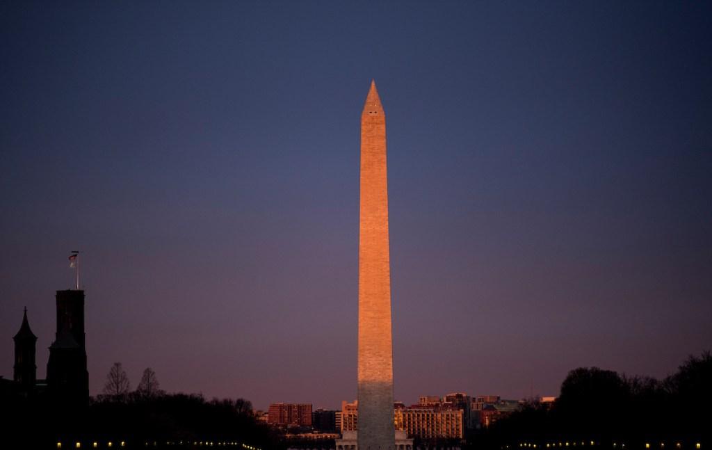 A brief burst of sunlight hits the Washington Monument at sunrise on Thursday. (Bill Clark/CQ Roll Call)
