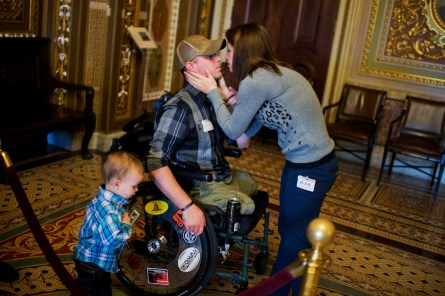 Luke Cifka, of Olympia, Wash., an Army veteran who was wounded in Afghanistan, shares a moment with his wife Kaitlin, and son Wyatt, 2, in the Senate Reception Room,December 9, 2014. (