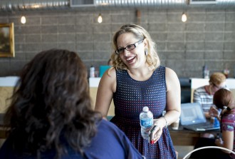 Sinema shakes hands with a constituent at Giant Coffee in Phoenix during a campaign trip last August. (Bill Clark/CQ Roll Call File Photo)