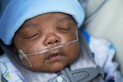 UNITED STATES - FEBRUARY 23: Taylormatthias Wilson-Williams, 2 months, is pictured outside of a water distribution area at the St. Mark Baptist Church in Flint, Mich., February 23, 2016. He was born 12 weeks premature and his mother, Tiantha Williams, believes that it is related to her home's contaminated drinking water. He must use a heart monitor and breathing machine. The water supply was not properly treated after being switched from Lake Huron to the Flint River and now contains lead and iron. (Photo By Tom Williams/CQ Roll Call)