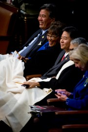 UNITED STATES - JANUARY 20: Reps. Mark Takano, D-Calif., left,  Alma Adams, D-N.C., and other members, huddle under a blanket in the Capitol's House chamber before President Barack Obama's State of the Union address, January 20, 2015. (Photo By Tom Williams/CQ Roll Call)