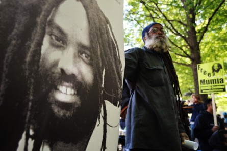 143344021 protestor stands next to an image of mumia gettyimages 445x297 Mumia Abu Jamal Case Reverberates in Senate Nomination Fight