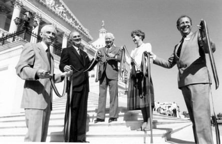 (Original Caption) ZIPPER-DE-DOO-DA: To dramatize North Carolina's interest in textile import legislation, Tar Heel Congressmen display a 65-foot zipper on Capitol steps. L-R: Reps. Charles Whitley, Bill Hefner and Tim Valentine, and Carole Cutcher and Ralph Gut of Ideal Fasteners. (Dean Brown/CQ Roll Call Photo)