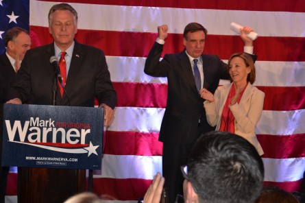 Sen. Mark Warner, D-Va., (right), joined on stage by fellow Virginia Democrats Sen. Tim Kaine (far left) and Gov. Terry McAuliffe (left), signals victory as minutes before midnight on Nov. 4 as his wife, Lisa Collis (far right), looks on. (Warren Rojas/CQ Roll Call)