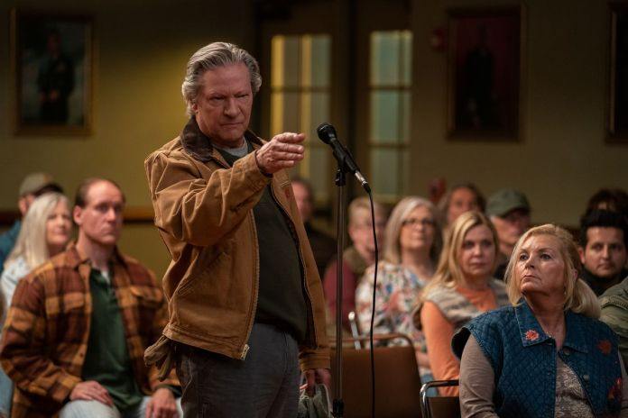 Chris Cooper stands at a microphone at a public meeting in Irresistible.