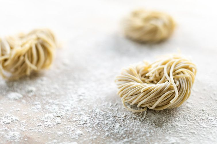 Nests of fresh pasta on a floured surface
