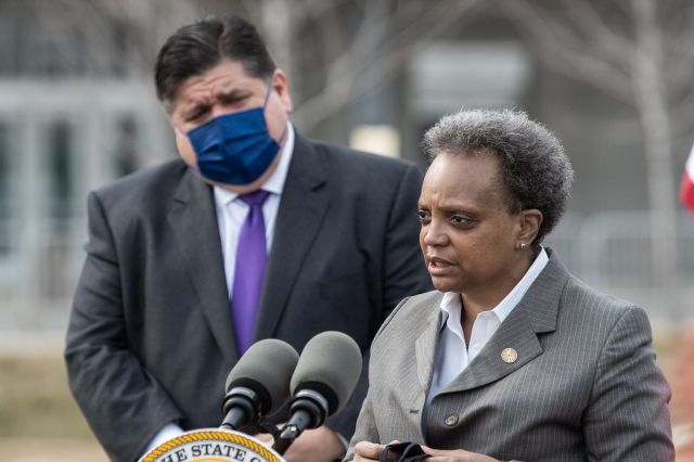 Mayor Lori Lightfoot speaks as Gov. J.B. Pritzker listens during a news conference about the opening of the new COVID-19 mass vaccination in Chicago in March.