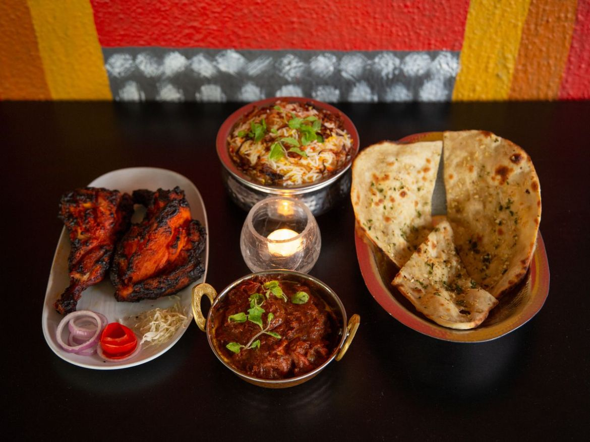 Four dishes of different materials and shapes hold various Indian-Chinese dishes including pita, tandoor-cooked meat, rice, and curry, on a dark tabletop near a colorful wall