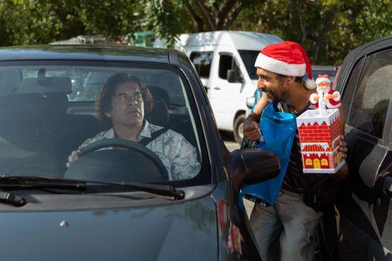 Leandro Hassum está sentado em seu carro parecendo alarmado quando alguém com um chapéu de Papai Noel o confronta