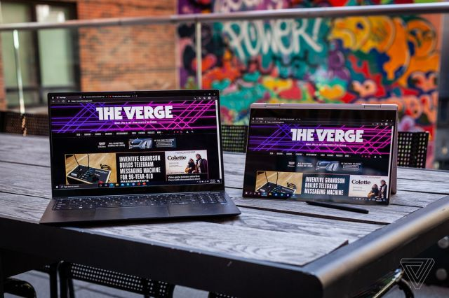 The Samsung Galaxy Book Pro open, and the Samsung Galaxy Book Pro 360 in tent mode, side by side on a picnic table. Both screens display The Verge homepage. The S-Pen lies in front of the Galaxy Book pro 360.