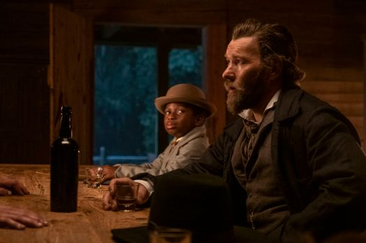 Slave-catcher Ridgeway (Joel Edgerton) and assistant Homer (Chase W. Dillon) sit at a bar together in Barry Jenkins' The Underground Railroad