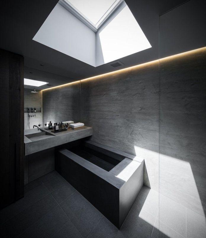 Полностью бетонная ванная комната с угловой бетонной ванной и потолочным окном над головой.