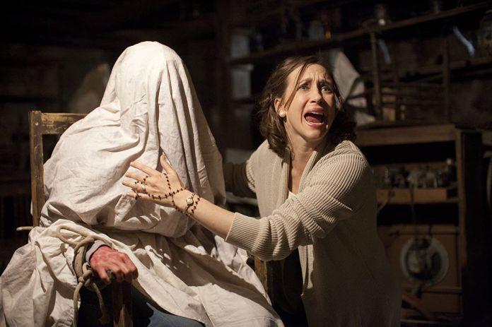 Lorraine Warren (Vera Farmiga) touches a woman covered in a sheet