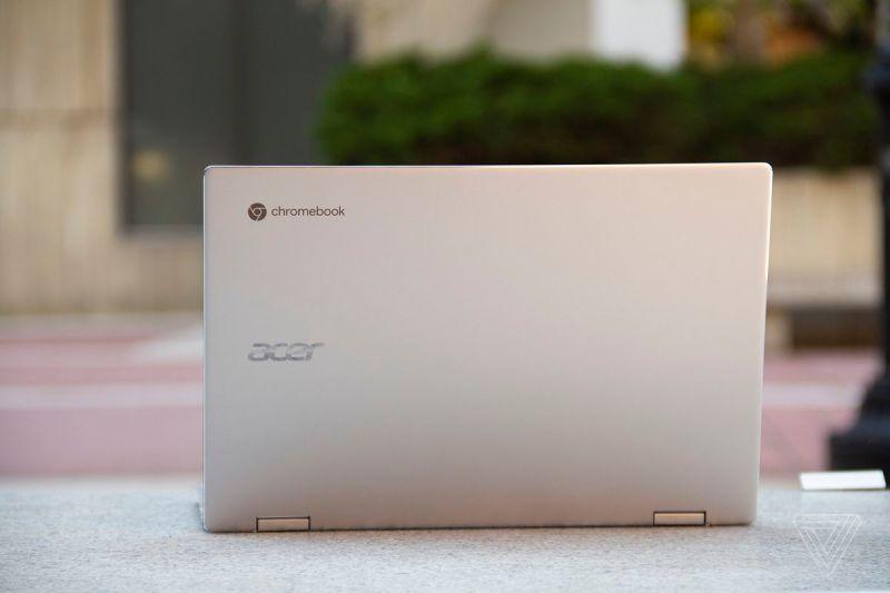 L'Acer Chromebook Spin 513 si apre, visto da dietro, su una panchina di pietra.