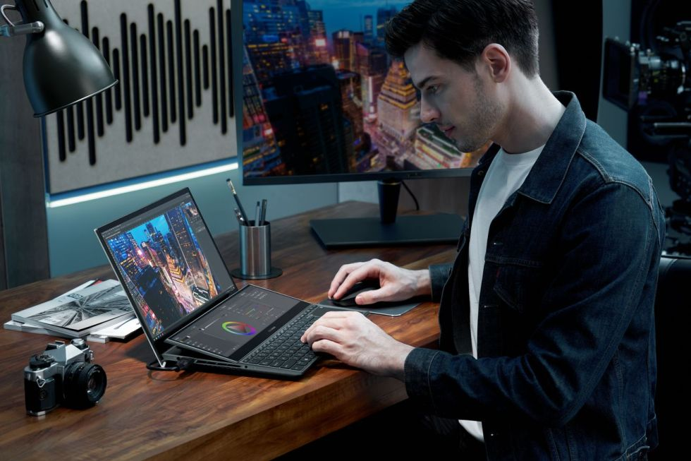A user types on the Zenbook Pro Duo 15 OLED in a low-lit office space.