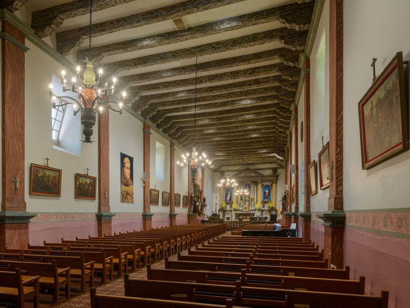 L'intérieur de la mission San Buenaventura à Los Angeles.  Il y a des rangées de bancs, de lustres et d'œuvres d'art sur les murs.  Il y a des poutres apparentes au plafond.