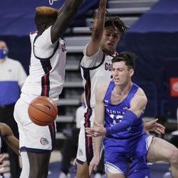 BYU goalie Alex Barcello, right, passes the ball past center Gonzaga Oumar Ballo, left, and forward Anton Watson during the second half of an NCAA college basketball game in Spokane, Wash., Thursday, January 7, 2021.