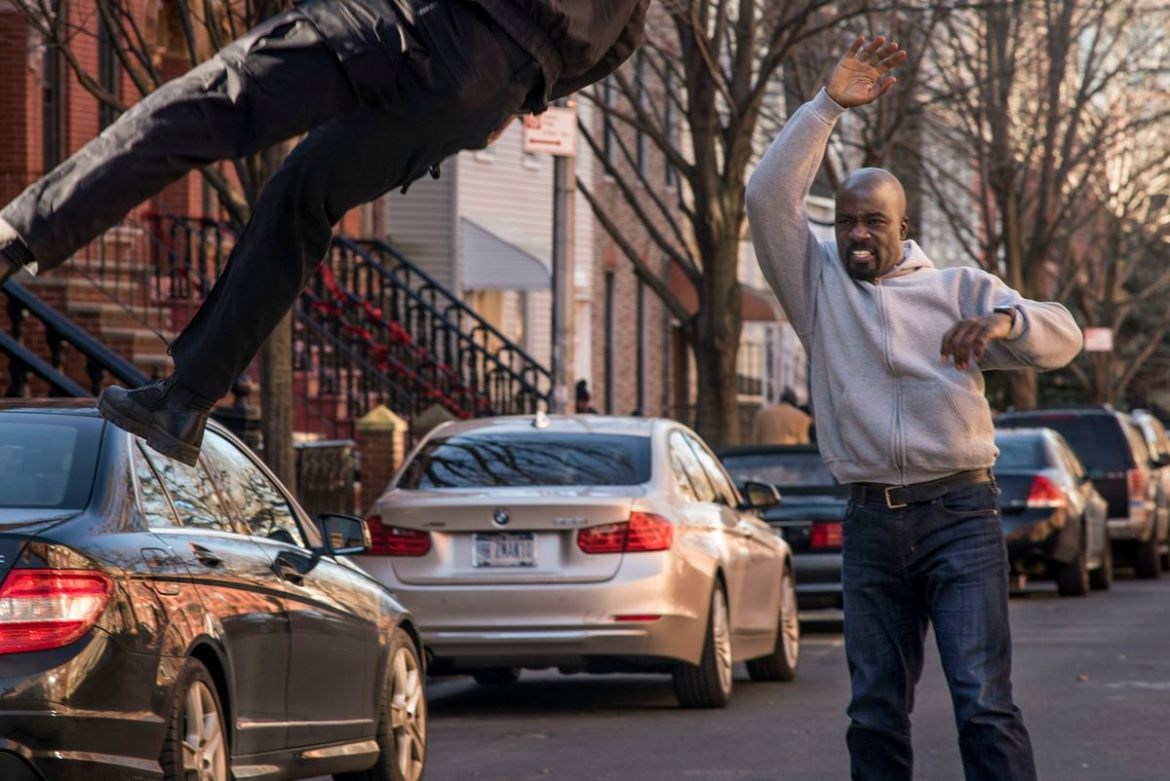 Luke Cage throws a bad guy in the street