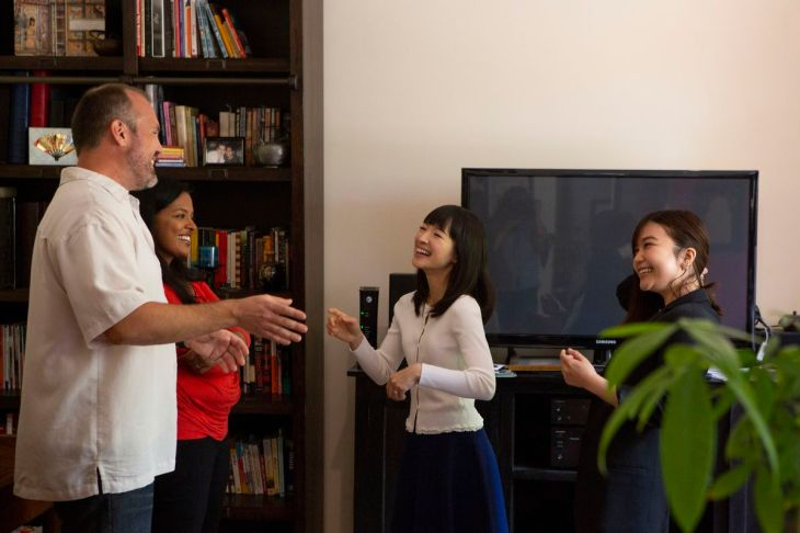 Kondo laughs in front of a bookshelf as a married couple and her interpreter look on