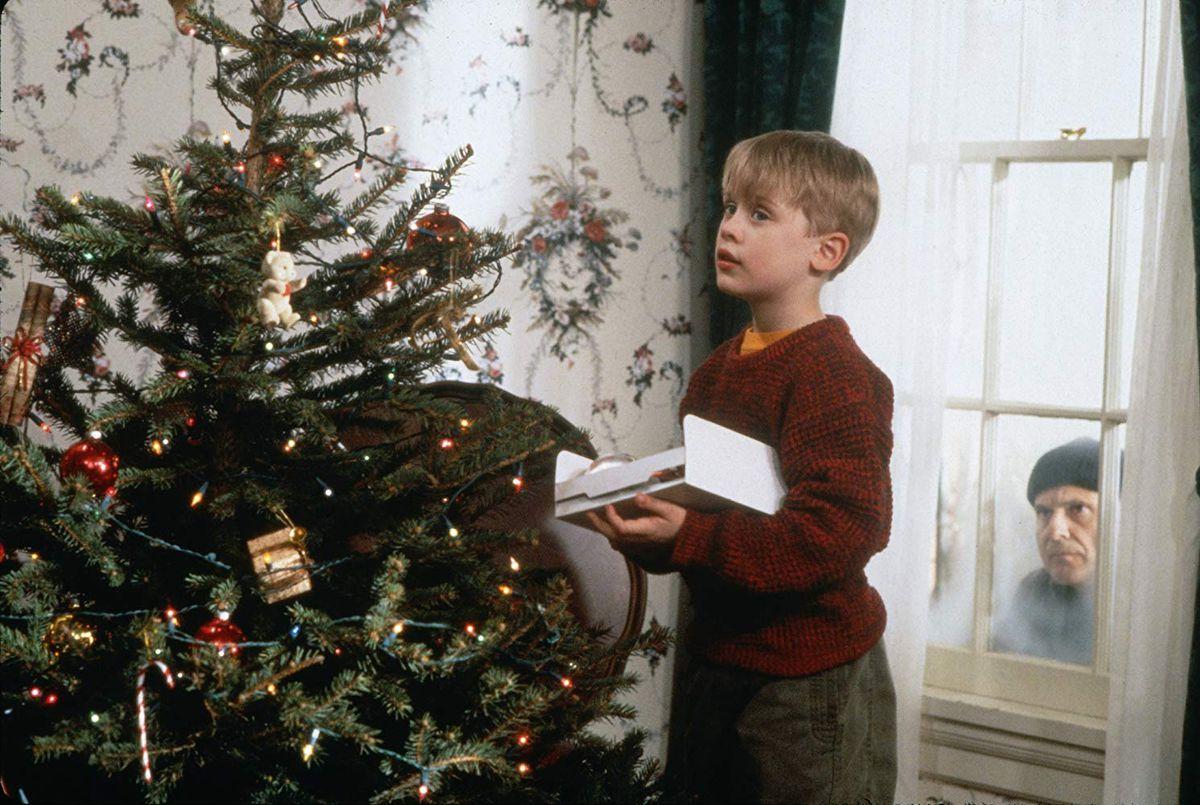 Kevin (Macaulay Culkin) decorates a tree while Harry (Joe Pesci) looks through a window.