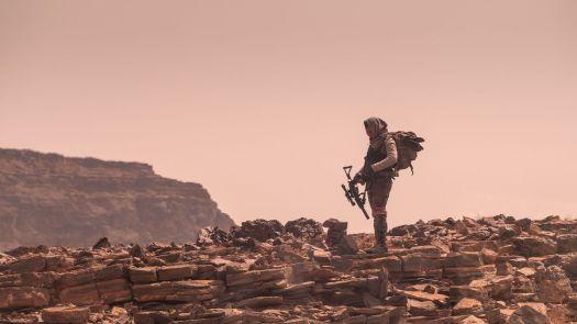 Ismael Cruz Córdova as Jerry stands in a barren Martian landscape in Settlers