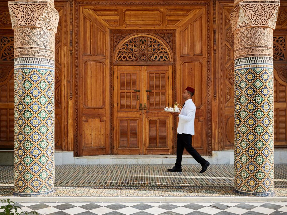 A server in a white jacket and red cap carries a silver tray of tea past a massive wall of ornate woodwork and between two decorative marble columns
