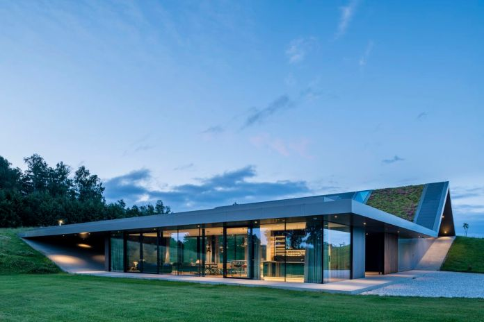 Плоский уровень дома имеет стеклянные стены, выходящие на жилое пространство, в то время как его зеленая крыша поднимается в вершину.