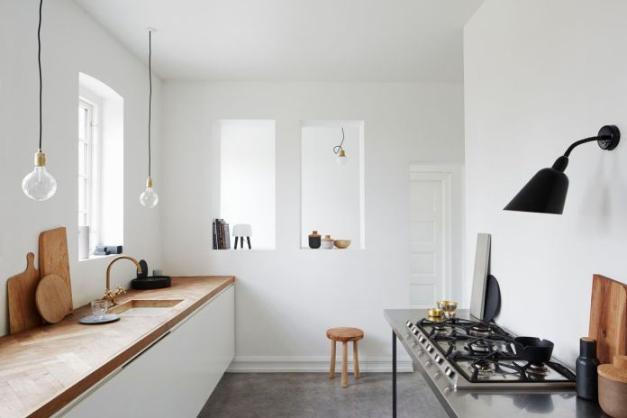 A minimalist kitchen with cement floors, a wood countertop, and exposed bulbs.