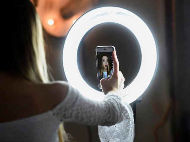 A person using a ring light to take a selfie.