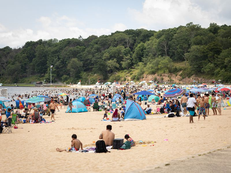 hundreds of people gathered on the shores of a lake beach.