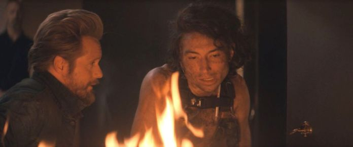 Ezra Miller in The Stand episode 6 speaking to Randall Flag by a hotel room fire