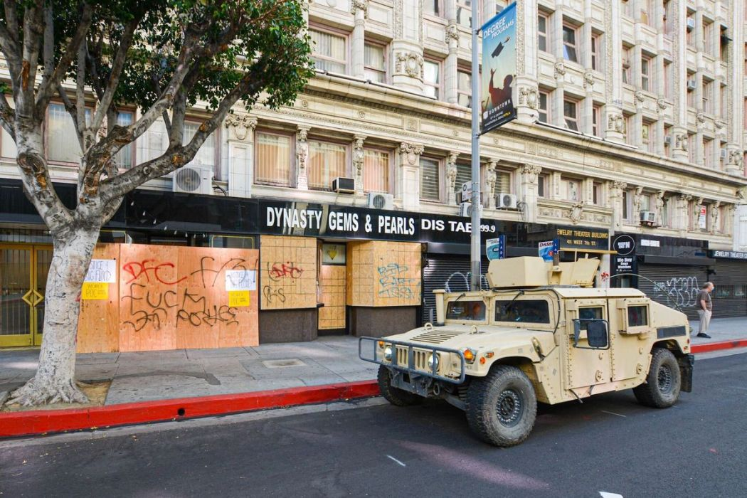 A national guard vehicle sits in front of a boarded up restaurant.
