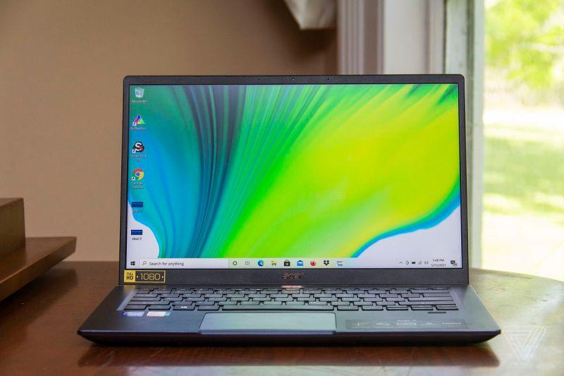 L'Acer Swift 3X si apre su un pianoforte visto di fronte.  Lo schermo mostra una sfumatura blu, verde e bianca.