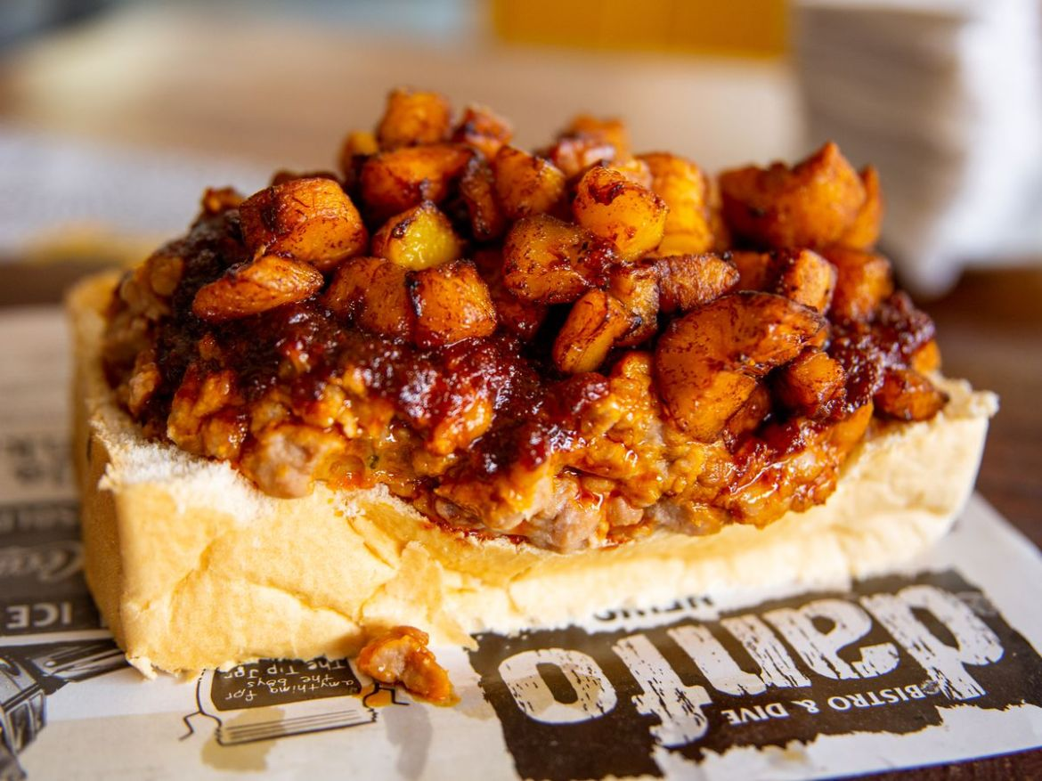 Cubed plantains and beans in a dark sauce pile on top of a large slice of white bread on top of a newspaper-like placemat with the name of the restaurant Danfo