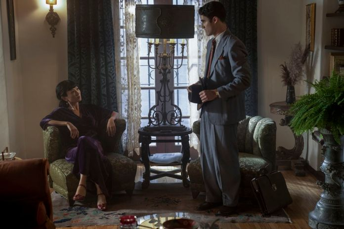Darren Criss, in a grey tailored suit, stands over a smirking Michelle Krusiec, sitting cross-legged in a plush chair.