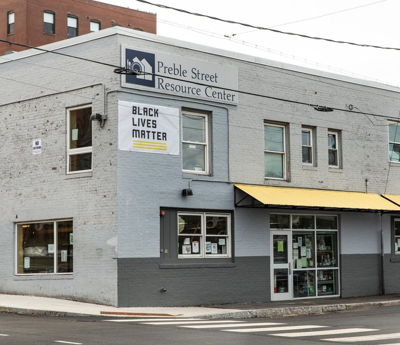 """Preble Street Resource Center in a grey brick building on a corner with a """"Black Lives Matter"""" sign"""