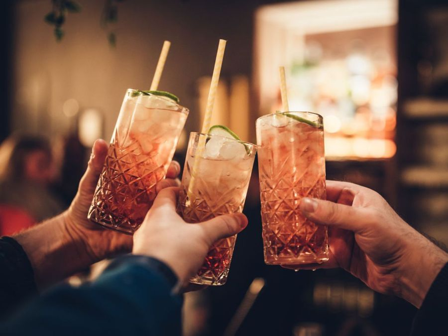 three people clinking cocktail glasses