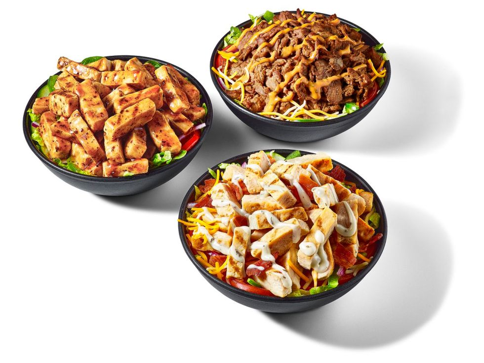 Three bowls on white background contain protein bowls from Subway restaurant chain. Two contain chicken, and one bowl contains steak.