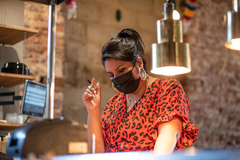 A woman behind a counter wearing a mask and holding a Sharpie poised to write