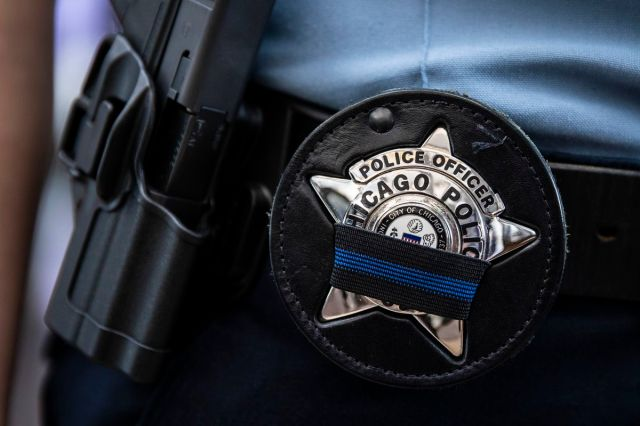 A Chicago police officer wears a blue and black band on her badge as she walks into the Leighton Criminal Courthouse to attend the Tuesday bond hearings for two brothers charged after the fatal shooting of Chicago Police Officer Ella French.
