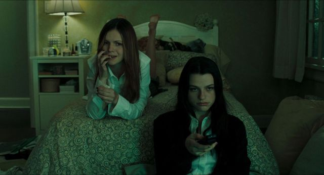 Teens Katie (Amber Tamblyn) and Becca (Rachael Bella) watch television on Katie's bed in a screenshot from The Ring