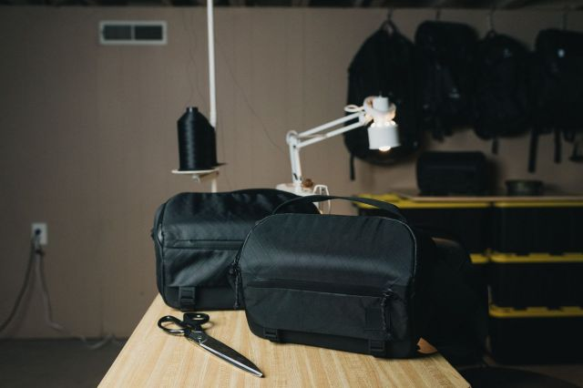 Two black Moment Rugged Camera Sling bags on a wooden table with a lamp in the background