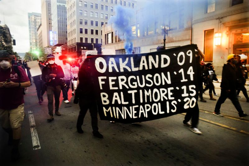 "A mid shining traffic lights, smoke, and a sinking sun, a group of protesters march through the street. They are led by two people in black, holding a black flag with bold white text that reads, ""Oakland '09 Ferguson '14 Baltimore '15 Minneapolis '20."""